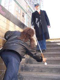 VISIONS rehabilitation instructor teaches participant to safely travel down subway stairs using a prescribed long cane
