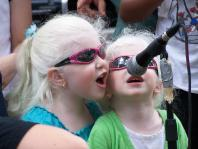 VCB Participants, sisters, sing into a microphone
