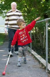 A child who is blind navigates VCB using the rails and a prescribed long cane